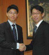 英国チーム受け入れに向け、協力の握手を交わす吉田好彦理事(左)と秋山浩保市長=柏市役所で