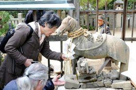 昨年3月、富丘八幡神社を訪れ丹波佐吉作の神馬を調査する磯辺教授。講演会では佐吉の作品の魅力を紹介する=土庄町渕崎