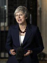 閣議後、EU離脱条件に関する協定素案が承認されたことを首相官邸前で発表するメイ英首相=14日、ロンドン(AP=共同)