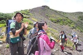 富士山の植生について説明する鈴木渉さん(左)=11日、富士山宝永火口付近