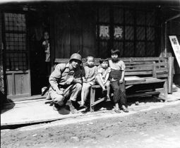 三菱造船所小ケ倉寮(現在の長崎市上戸町)にあった海兵隊宿舎の警備をする米兵と子どもたち。敗戦から間もない時期だが、子どもが米兵を恐れる様子は見られない=1945年9月29日(長崎原爆資料館提供)