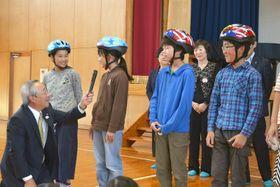 ヘルメットを試着する児童ら。「友達とかぶって遊びに行きたい」の声も(20日午後、南国市国分の国府小学校)