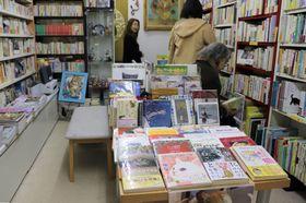 ネコにまつわる小説や写真集が所狭しと並び、訪れた客がゆったりと会話や品定めを楽しむ店内(京都市中京区・猫本サロン サクラヤ)