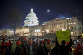 米議会の前で移民政策を巡って抗議行動を行う人々=21日、ワシントン(ゲッティ=共同)