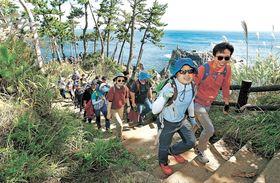 雄大な景色が広がる海岸沿いの遊歩道を歩く参加者=7日午前11時10分ごろ、気仙沼市唐桑町