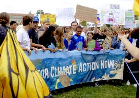 米ホワイトハウス周辺で、地球温暖化対策の強化を求めて米国の若者らとデモ行進するトゥンベリさん(中央)=13日(共同)