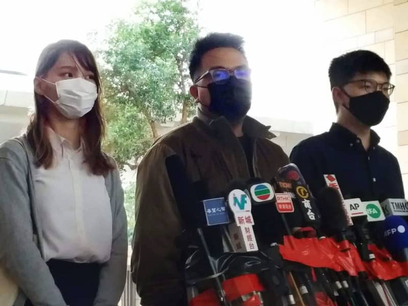 11月23日、香港の裁判所に出廷した周庭氏(左)、黄之鋒氏(右)ら民主活動家の3人(共同)