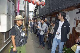 さんぽマイスターのガイドを受けながら、八戸市内の横丁を散策する参加者たち=5日午後