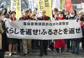 福島第1原発事故で国や東京電力に損害賠償を求めた訴訟の判決で、横断幕を掲げ横浜地裁に向かう原告ら=20日午前