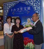 入場者5万人目となり、柳原館長(右端)から記念の図録などを受け取る小林さん(中央)=京都市左京区・京都国立近代美術館