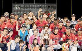 試合後のグラウンドで、ファンや選手らと笑顔で記念撮影をする駒田徳広監督=中央(10日夜、高知市の高知球場=久保俊典撮影)