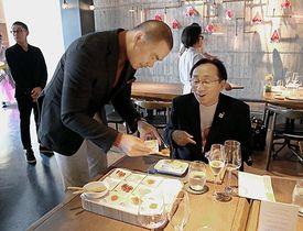 三村知事(右)にのっけ丼をアレンジした料理を取り分けるチャン氏=11日午後、台北市(県提供)