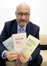 出版された3作を手にする英国の出版社「レッド・サークル」のリチャード・ネイサンさん=2018年12月、ロンドン(共同)