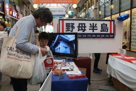 「長崎・野母半島パワースポット発信塾」のブースを訪れた市民ら=長崎市、ベルナード観光通り