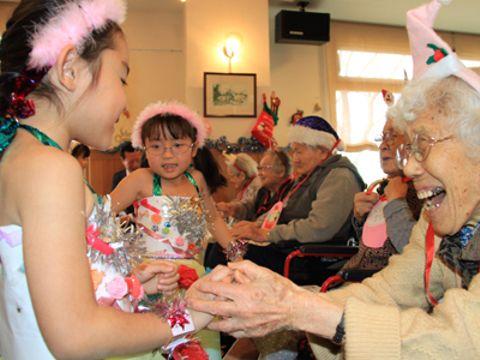 園児の手を取り感謝の気持ちを伝えるお年寄りたち=13日、下関市