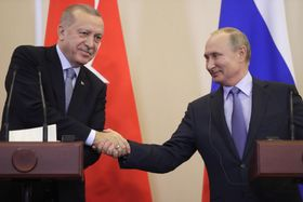 22日、ロシア南部ソチで握手するロシアのプーチン大統領(右)とトルコのエルドアン大統領(タス=共同)