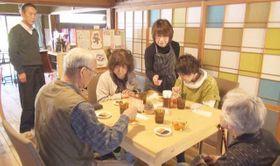 チョコレートの説明をしながら接客する青木代表(中央)と康廣さん(左奥)
