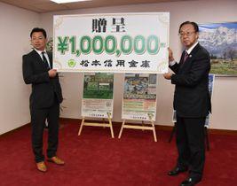 田中理事長(右)から100万円の目録を受け取った神田社長