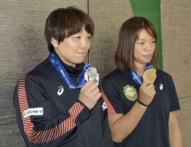 レスリングの世界選手権から帰国し、獲得したメダルを手にする川井梨紗子(右)と皆川博恵=23日、成田空港