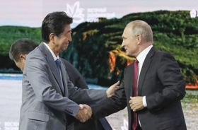 東方経済フォーラムの全体会合で、ロシアのプーチン大統領(右)と握手する安倍首相=12日、ロシア・ウラジオストク(代表撮影・共同)