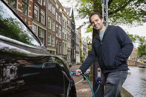 運河沿いの街角で、電気自動車に充電するファンデブロン創業者のマティス・ヒフラー=19年6月、アムステルダム(共同)