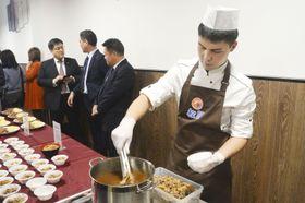 ロシア1号店となるモスクワの「松屋」で、試食用の牛めしを準備するロシア人男性=19日(共同)