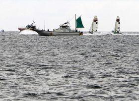 セーリングのW杯江の島大会で、漁船の近くを通る競技艇=11日