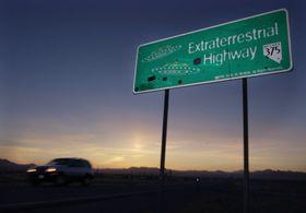 米西部ネバダ州の「エリア51」の近くを通る道路。看板には「地球外ハイウエー」と書かれ、UFOが描かれている=2002年4月(AP=共同)