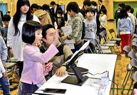 再現した作業員の手のひらの感触を楽しむ児童