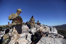 トルコ軍と共闘するシリア反体制派の戦闘員ら=19日、シリア北西部アフリン近郊(ロイター=共同)