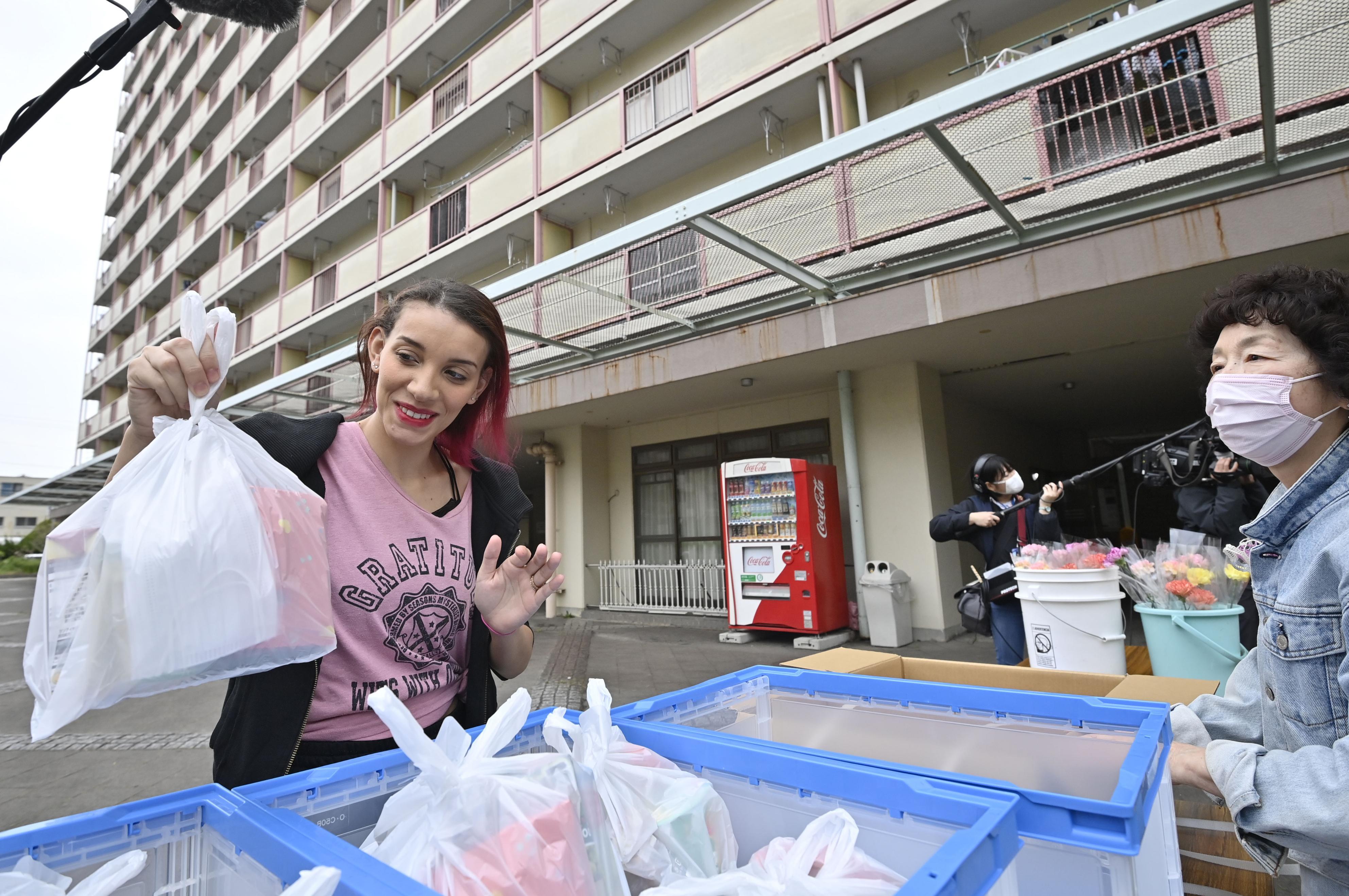 名古屋市の「九番団地」で、NPOが配布した食料を手にするブラジルからの住民=26日午後