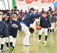 佐藤龍世選手(中央)の指導で守備練習に励む児童たち