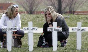 コロンバイン高校銃乱射事件の犠牲者の名前が記された十字架を前に座り込む、同校の卒業生(右)=20日、米西部コロラド州(AP=共同)
