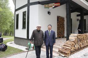 開業したレストラン「ル・ゴロワ フラノ」を背に記念写真に納まる倉本聡さん(左)=28日午前、北海道富良野市