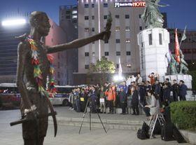 3日、韓国・釜山の日本総領事館近くに置かれている徴用工像(左)の前で開かれた市民団体の集会(共同)