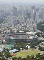 2020年の東京五輪開幕に向けて、建設工事が進む新国立競技場。奥は新宿の高層ビル群=11日午後、東京都新宿区(共同通信社ヘリから)