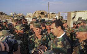 22日、シリア軍の兵士たちと話すアサド大統領(中央右)。大統領府のフェイスブックから=シリア北西部イドリブ県(AP=共同)