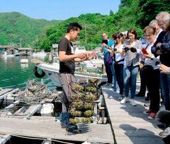 養殖いかだの下からアコヤガイを引き上げる様子をカメラに収めるスイス宝飾職人協会員ら=25日午後、宇和島市三浦西
