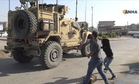 21日、シリア北東部カミシュリで、米軍の車両にジャガイモを投げる住民ら(シリアのクルド系通信社ANHA提供・AP=共同)