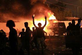 イラク南部バスラで、警察車両を燃やす反政府デモ隊(AP=共同)