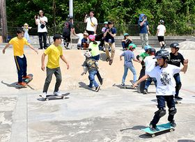 スケートボードの鬼ごっこで韓国選手(左側)と子どもたちが交流した=寒河江市・寒河江スケートパーク