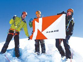 5500メートル峰の頂上で、北日本新聞社旗を掲げる隊員=10日