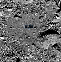 探査機オシリス・レックスが岩石を採取する予定の小惑星ベンヌのクレーター。中央の黒い模様は探査機のイメージ(NASA提供・共同)
