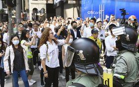 香港中心部の金融街セントラルで、警官隊(右手前)に抗議する市民ら=11日(共同)