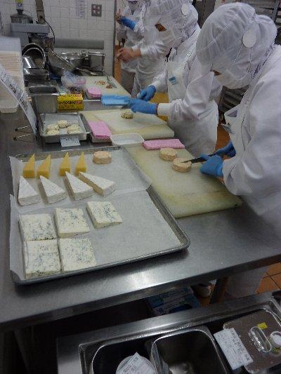 ■各種のチーズを切り分ける作業員