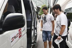AIを活用した配車の実証実験で、タクシーに乗り込む外国人観光客=21日午前、金沢市
