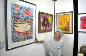 鮮やかな色使いで植物や動物を描いた作品を紹介する春美さん
