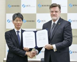 航空機の先進技術協力で合意し、握手する経産省の磯崎仁彦副大臣(左)とボーイングのハイスロップCTO=15日午後、経産省