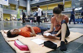 北海道の地震の後、新千歳空港のロビーに敷いた毛布の上で過ごすフランスからの観光客=9月8日