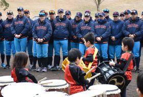 歓迎セレモニーで、園児の演奏に笑みをこぼす建国大の野球部員